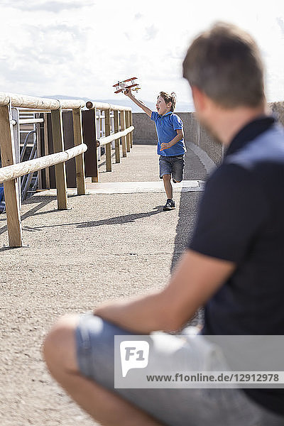 Father looking at son running with toy plane