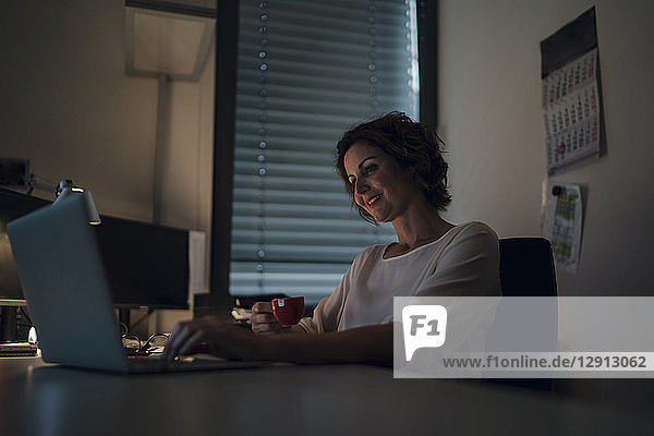 Businesswoman working overtime  using laptop  drinking coffee