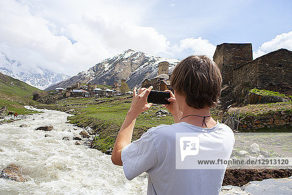 Georgia,  Ushguli,  Photographer taking pictures of the historic denfense towers made from stone
