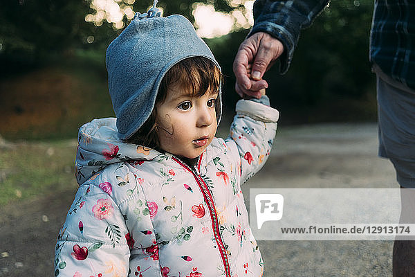 Portrait of fashionable little girl walking hand in hand with her grandfather in autumn