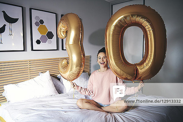 Young happy woman with golden balloons  celebrating her birthday
