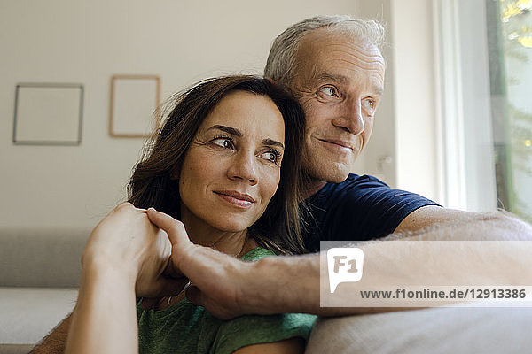 Smiling mature couple sitting on couch at home