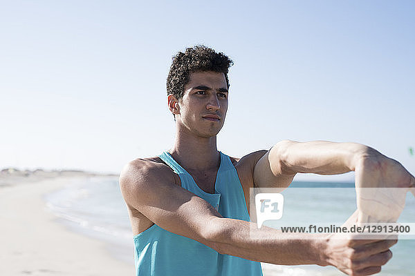 Spain  Canary Islands  Fuerteventura  young man stretching his arm on the beach