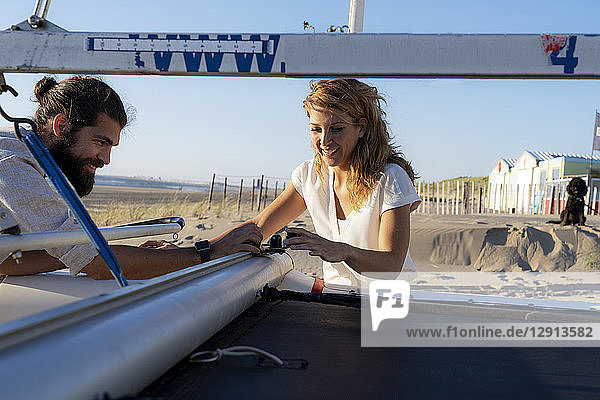 Young couple getting sailing boat ready