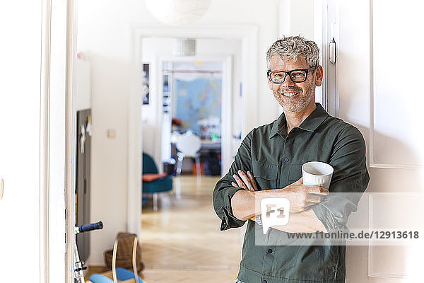 Portrait of smiling mature man with coffee cup leaning against door case at home