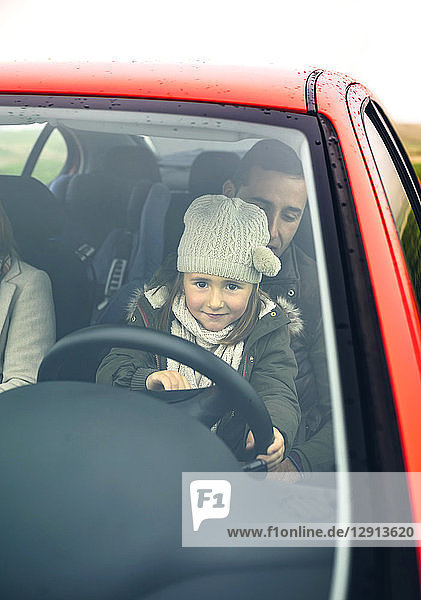 Little girl with wool cap driving car sitting on father's lap