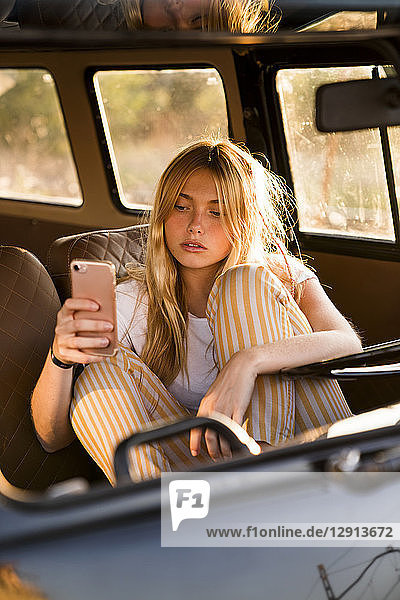 Young woman sitting in a van using cell phone