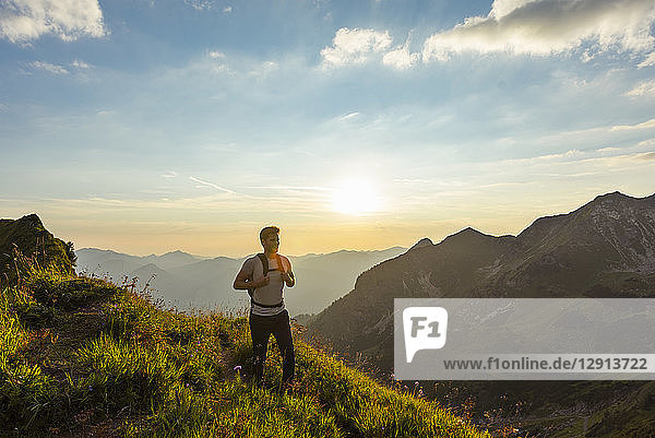 Germany  Bavaria  Oberstdorf  man on a hike in the mountains at sunset
