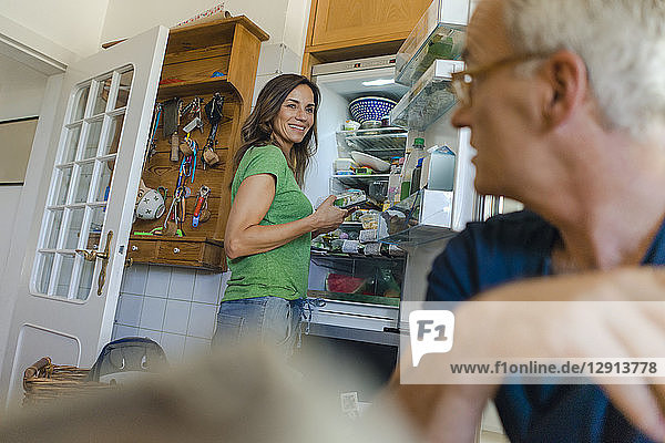 Mature couple at home with woman standing at refrigerator