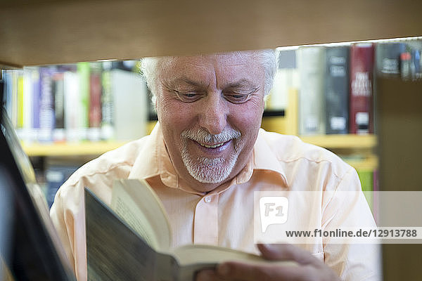 Portrait of smiling senior man in a city library reading book