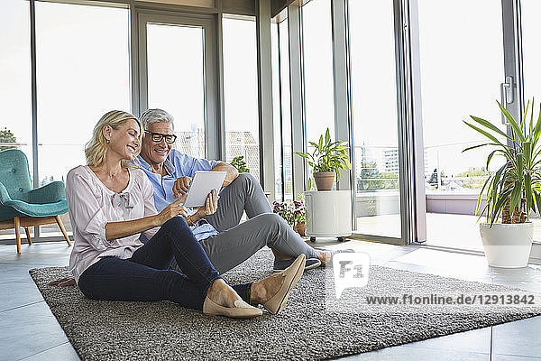 Smiling mature couple relaxing at home sitting on carpet sharing tablet