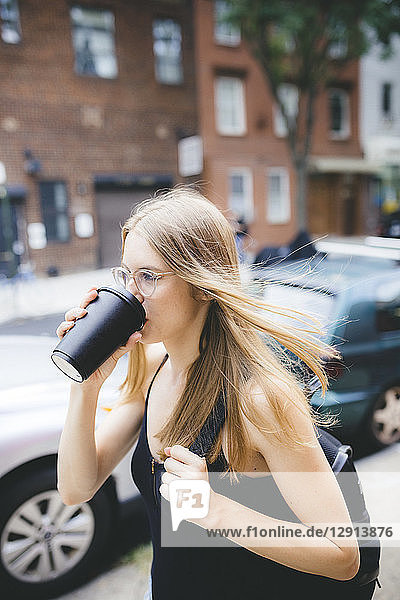 Young woman drinking cup of coffee in NYC