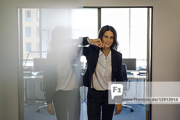 Successful businesswoman standing in office door  smiling