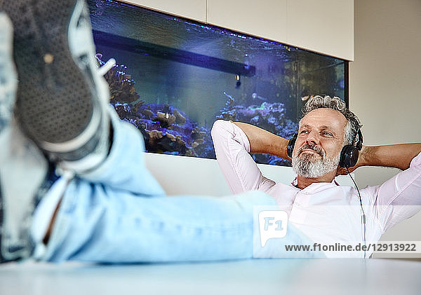 Relaxed mature man listening to music with headphones in front of aquarium