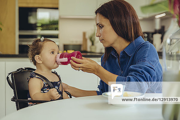 Mother helping baby daughter drinking water from bottle in kitchen