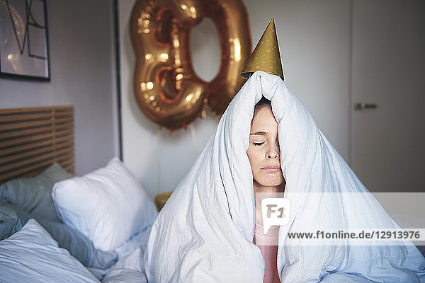Sad woman celebrating her birthday  sitting on bed under blanket