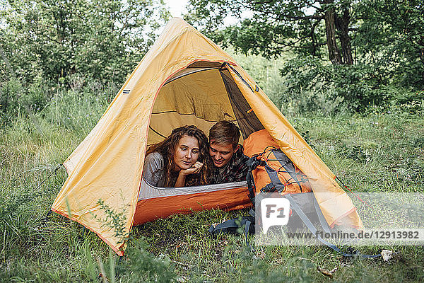Young couple camping in nature  lying in tent  taking a break