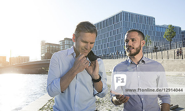 Two businessmen talking at the riverbank
