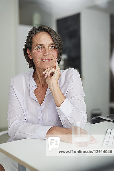 Portrait of pensive mature businesswoman sitting at desk