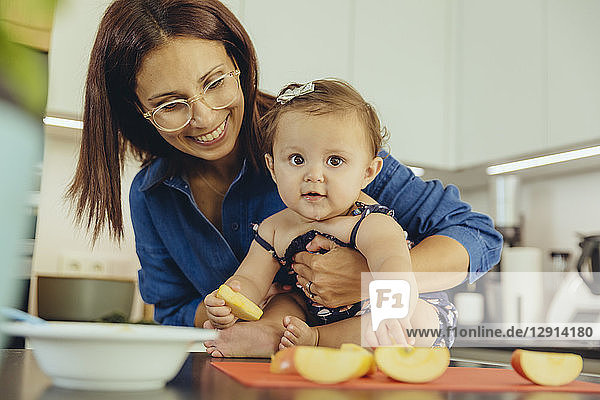 Mother and baby daughter eating apple chunks in kitchen