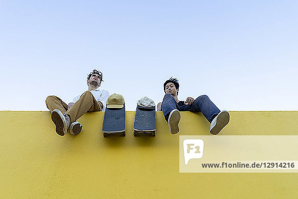 Two young men with skateboards sitting on a high yellow wall