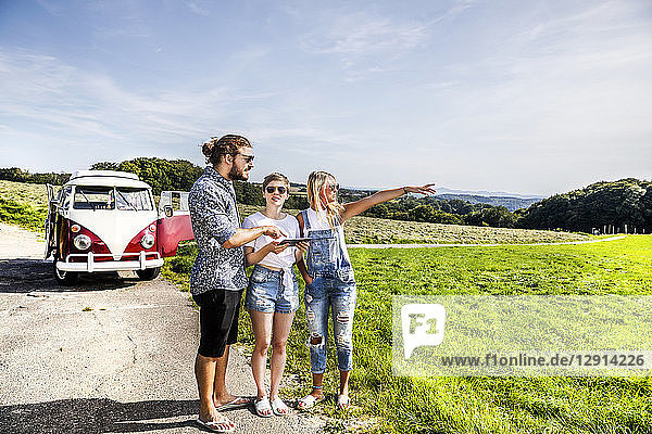 Friends with tablet outside van in rural landscape