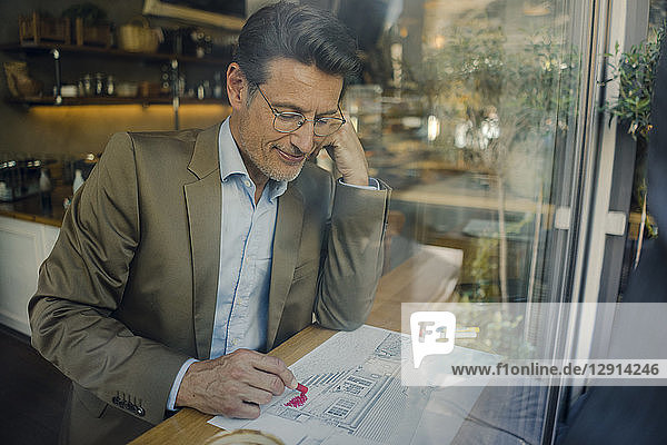 Mature businessman sitting in coffee shop  drawing outline of a house