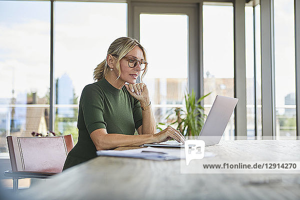 Mature woman using laptop on table at home