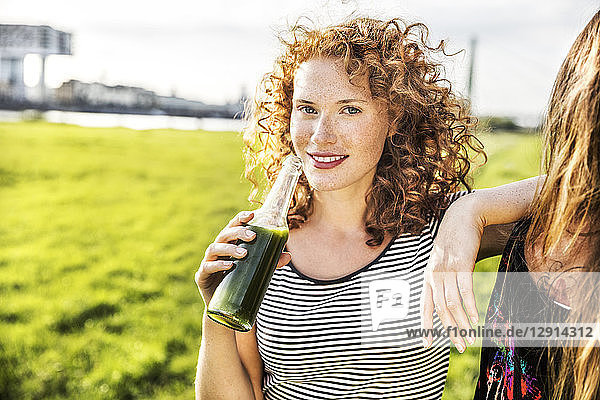 Germany  Cologne  portrait of redheaded young woman enjoying beverage