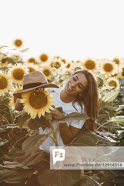 Portrait of a young laughing woman with straw hat  standing in a field of sunflowers