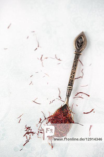 Spoon with saffron threads on light ground