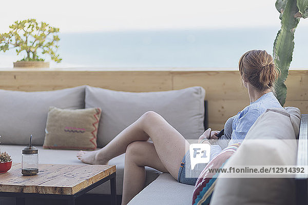 Morocco  Lounge  young woman sitting on couch  holding smartphone