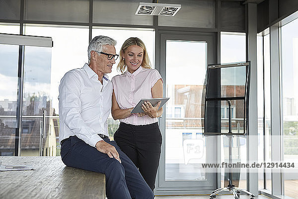 Businessman and woman standing in office  discussing project  looking at digital tabet