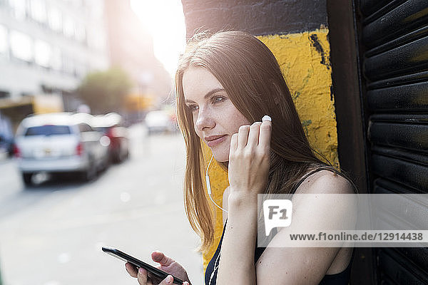 Young woman leaning on street corner  listening music  using smartphone