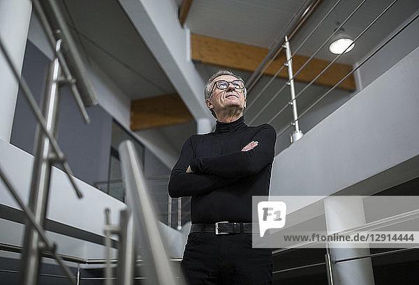 Confident senior businessman standing in office hallway
