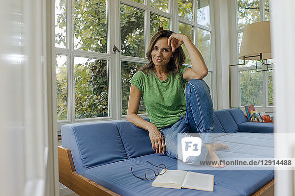 Smiling mature woman sitting on couch at home with book