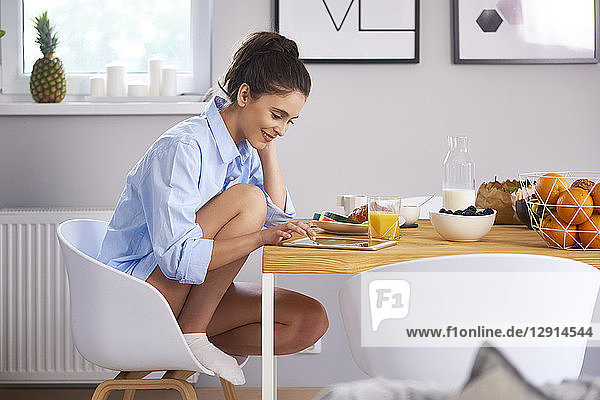Young woman at home in kitchen  eatinng breakfast  using digital tablet