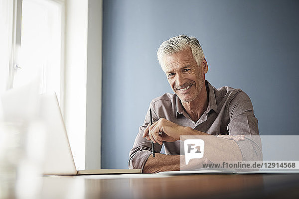 Portrait of confident mature man with laptop and documents at home