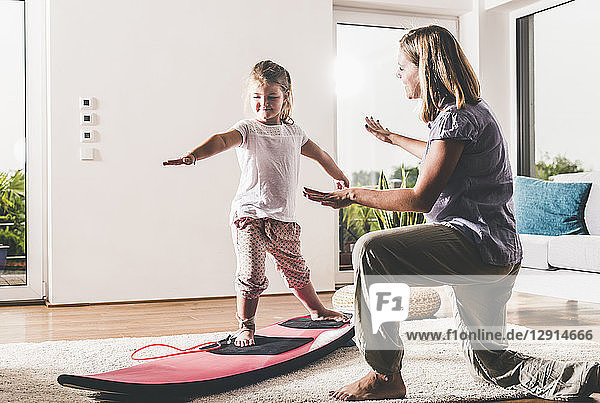 Mother and daughter exercising with surfboard in living room