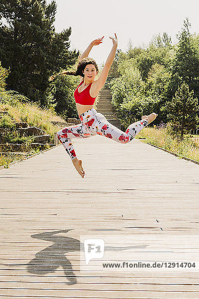 Young woman practicing Pilates in an urban park