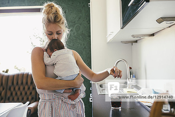 Mother holding newborn baby in kitchen while making tea Mother holding newborn baby in kitchen while making tea