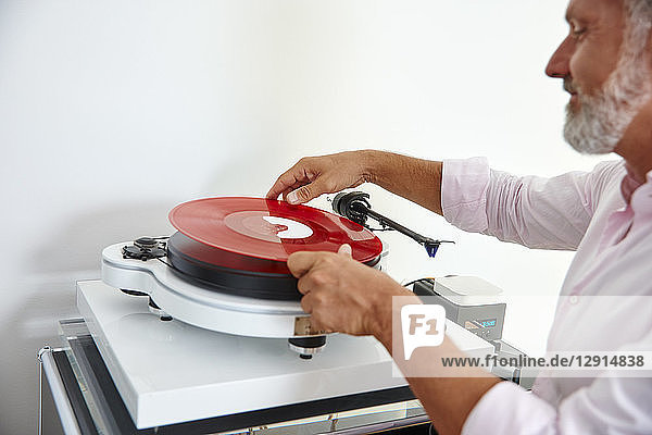 Mature man putting red vinyl record on record player