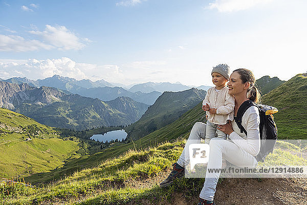 Germany  Bavaria  Oberstdorf  mother and little daughter on a hike in the mountains having a break