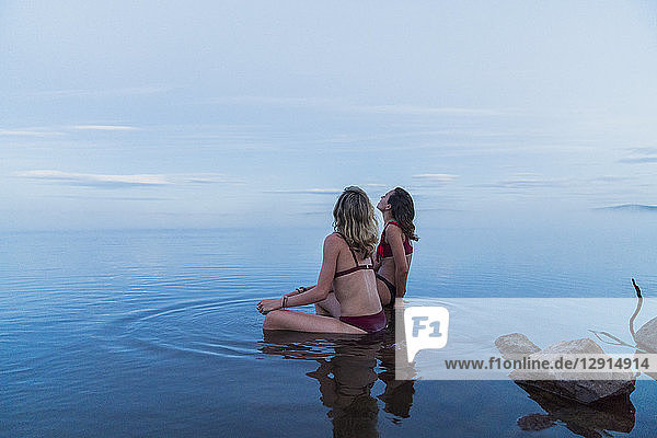Two young women wearing bikinis  sitting on a stone in a lake