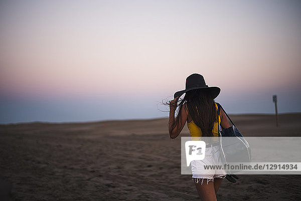 Back view of teenage girl with hat and shoulder bag walking on the beach at sunset