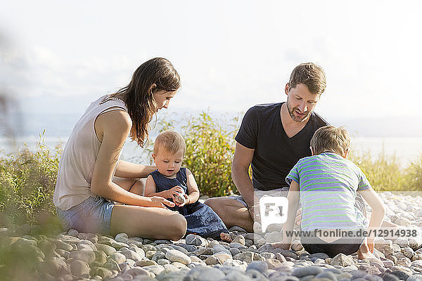 Germany  Friedrichshafen  Lake Constance  family playing with stones at lakeshore