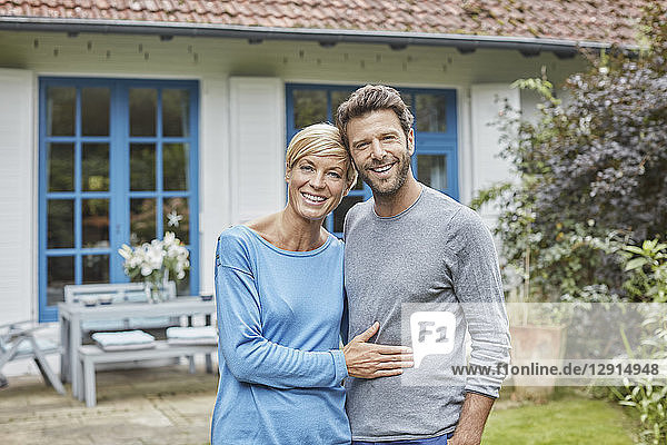 Portrait of smiling couple standing in front of their home