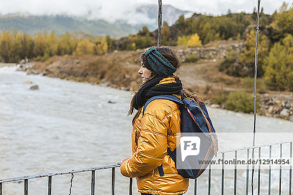 Spain  Alquezar  young woman with backpack standing on bridge