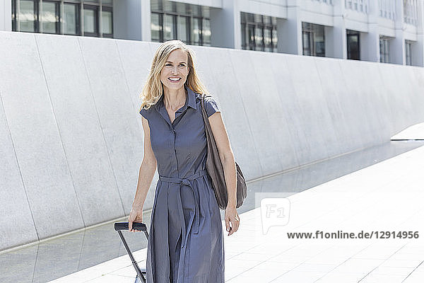 Smiling blond businesswoman with wheeled luggage