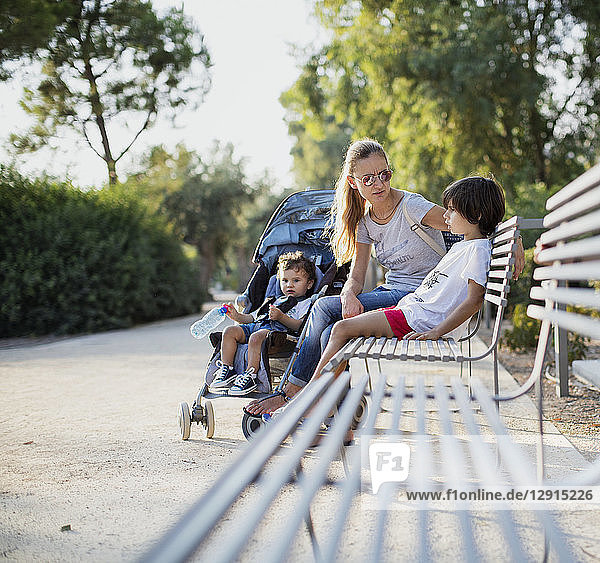 Mother sitting on park bench  talking to one of her sons